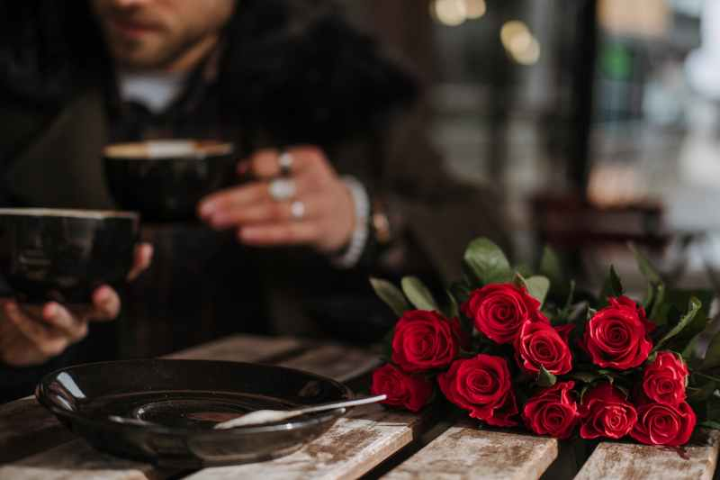 roses bouquet placed on table of street cafe near anonymous couple drinking cappuccino