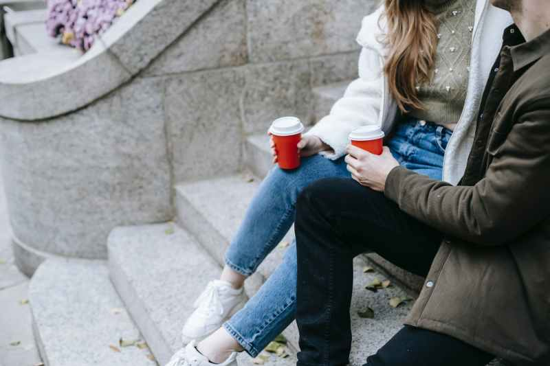 young man and woman sitting on stairs on street and having hot drinks