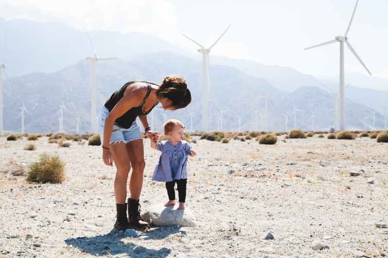 woman holding her child walking near windmills