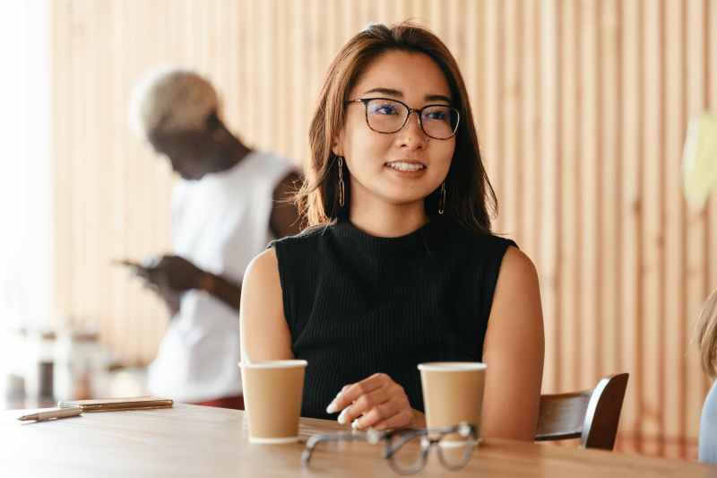 young pleasant asian woman in eyeglasses in cafe