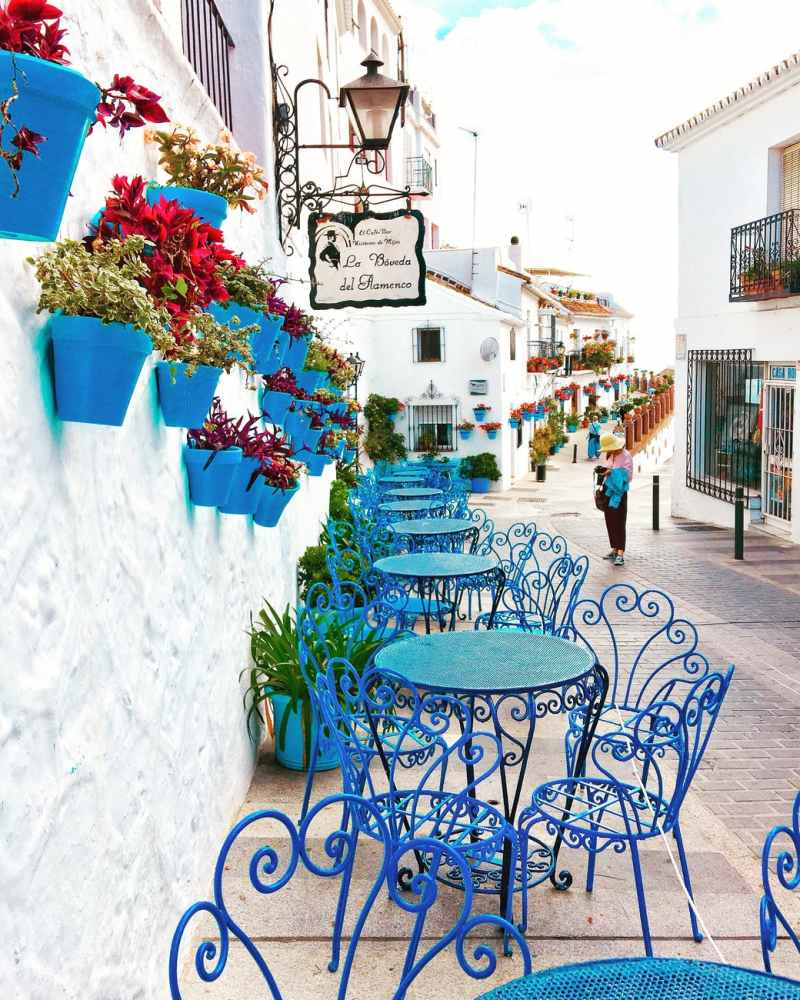 blue metal bistro sets near potted flowers and road