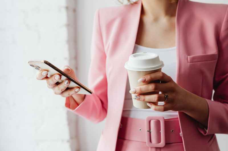 a woman holding a cup of coffee while using her smartphone