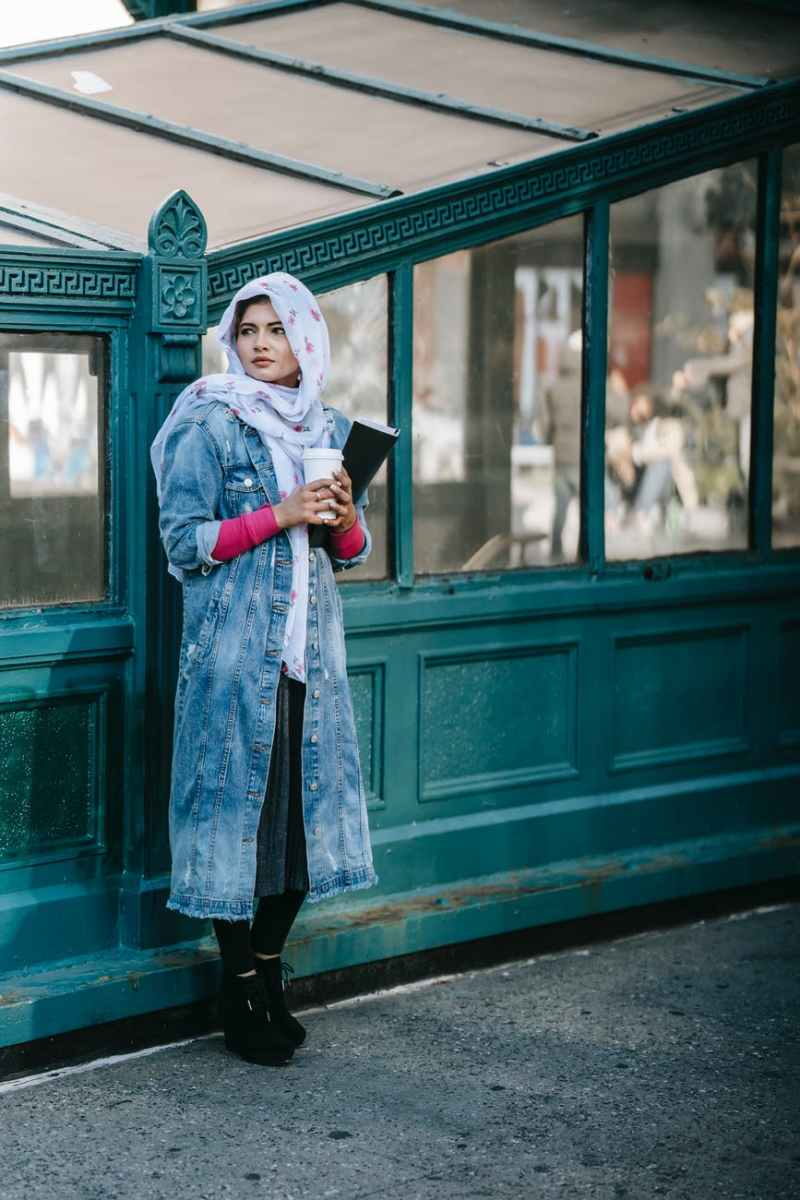 muslim lady standing on city street and looking away