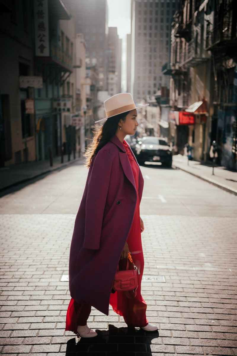 woman in red coat and white knit cap standing on sidewalk