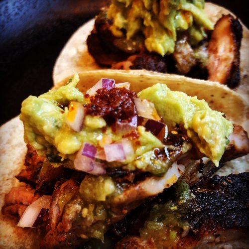 two larger corn tortillas, grilled and filled with grilled chicken and avocado, with ancho rub, guacamole & green tomatillo salsa