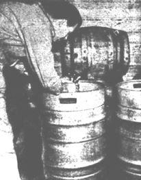 BEER DRUMS ON TRIAL - The Cascade Brewery Co. Ltd. has imported three trial steel drums, now being used on the Mainland for bulk beer. The brewery is investigating how they stand up to cartage, and whether they affect the flavour of beer. The steel drums eventually may replace the barrels made of Tasmanian blackwood, because there is a shortage of wood and coopers. Here Mr. F. G. Natty, cellarman at Hadley's Hotel, Hobart, is tapping one of the drums - The Mercury (Hobart) Friday 16 June 1950