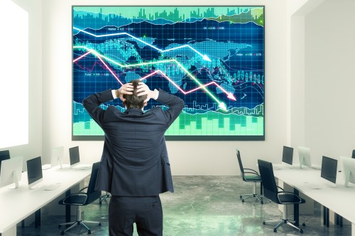 Businessman grabs the head in open space office with business chart at the wall