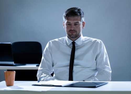 depressed man in a dark office