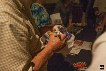 """Herb was also autographing various pieces of memorabilia; from die cast cars (as shown here) to copies of his new book, """"Blood, Sweat and Gears,"""" written by David G. Barnes."""