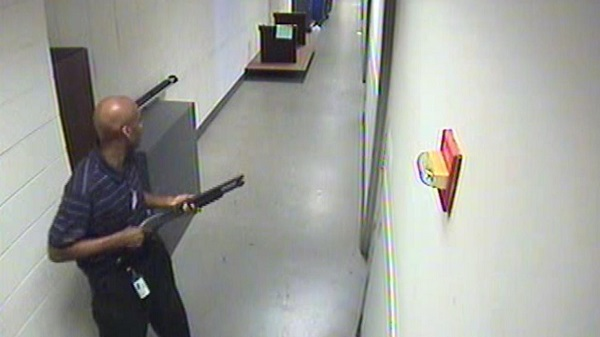 This image taken from security cameras shows Alexis moving through the hallways of Building #197 carrying a Remington 870 shotgun.
