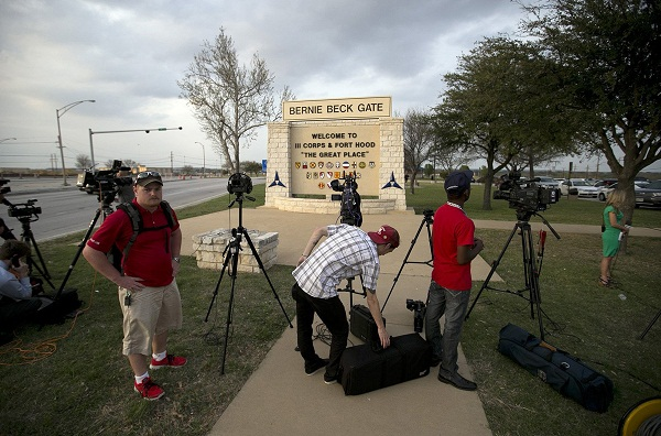 Media wait outside Fort Hood for an official statement Wednesday.