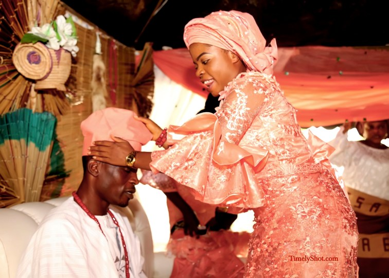 bride wearing the cap for her groom at yoruba traditional wedding