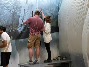 Charlotte Hohman stands on a bench inside a museum helping paint a mural of a Cretaceous forest with two other people