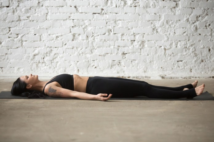 Corpse yoga pose for beginners to end a 30-minute active yoga session. It relax your body and mind after burning yoga session.