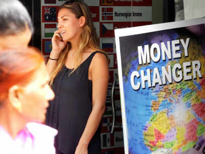 People stand outside a money changer office in Delhi. (TOI File Photo)