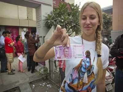 A Russian tourist pose with a new Rs 2000 note in New Delhi. (AP photo)