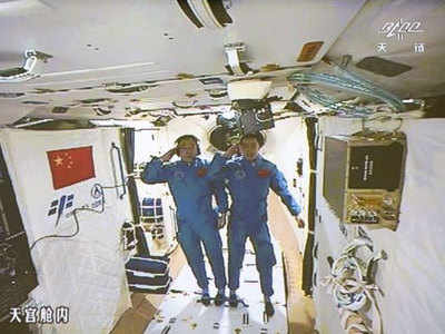 Chinese astronauts Jing Haipeng, (L) and Chen Dong salute in the space lab Tiangong 2. (AP file photo)