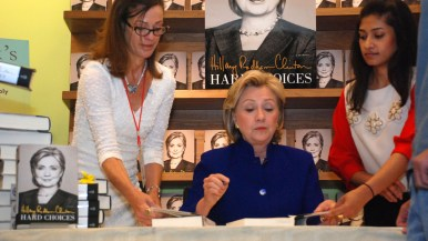 Nancy Warwick, store owner, hands a book to Hillary Clinton for signing.