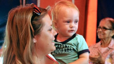 Mother comforts child after reacting to act in Worlds of Wonder sideshow at the San Diego County Fair.