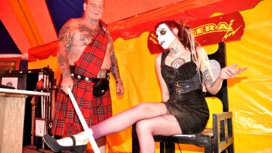 Red Stuart uses light tube to show Miss Electra is charged sitting on replica electric chair in Worlds of Wonder tent at San Diego County Fair.