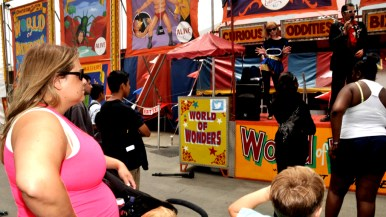 Fairgoers listen to pitch outside Worlds of Wonder tent at San Diego County Fair.
