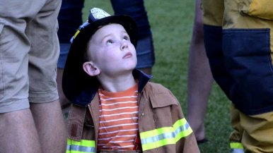 A young family member with the Escondido fire department looks up at the 30-story hotel.