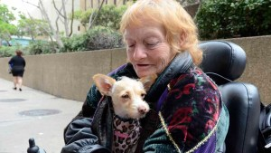 """Beverly Fisher and her dog, """"Mr. Wendall,"""" wait to veterinarian care at Golden Hall during a San Diego effort to help the homeless. Photo by Chris Stone"""