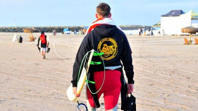 Service members carry their surfboards to competition at 7 a.m.