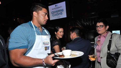 Manti Te'o serves hors d'oeuvres to guests at Donovan's Steak and Chop House downtown.
