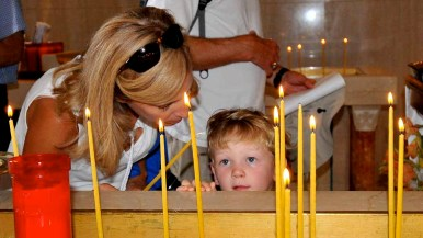 Visitors on the church tour pause to light candles as they enter. Photo by Chris Stone