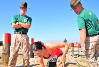 Drill instructors shout orders as a runner finishes the cargo rope obstacle. Photo by Chris Stone