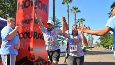 Joseph and Jessica Martinez cross the finish line together. They dedicated her run to their father who served as a Marine. Photo by Chris Stone