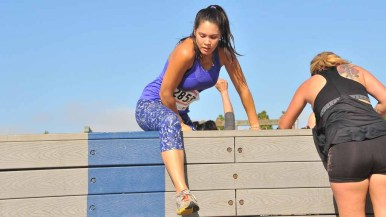 Participants make it over a 6-foot wall. Photo by Chris Stone