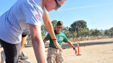 A drill instructor shouts orders as a competitor goes over a log. Photos by Chris Stone