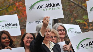 Former state Sen. Christine holds up sign endorsing Assembly Speaker Toni Atkins fo state Senate . Photo by Chris Stone