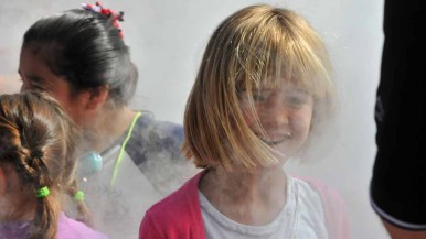 A young girl enjoys the vapor from a liquid nitrogen eruption. Photo by Chris Stone