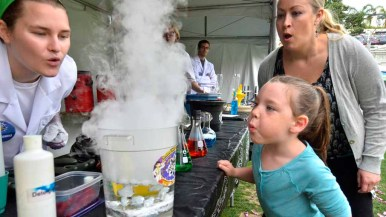 A young girl and her mother blow on the liquid nitrogen vapor at last year's San Diego Festival of Science and Engineering. Photo by Chris Stone
