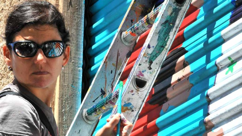 A student from the Atheneum Art School helped paint a mural on a building. Photo by Chris Stone
