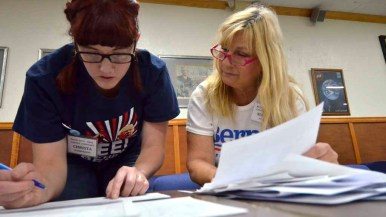 Caucus assistant Christa Wubbolding (left) tallies votes as names are read off ballots. Photo by Chris Stone