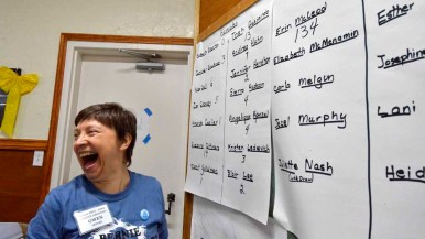 Caucus volunteer Gwen Lepard reacts at the vote total for Erin McLeod. Lepard posted the results as they were read. Photo by Chris Stone