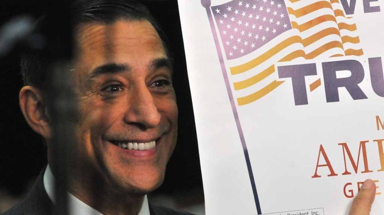 Rep. Darrell Issa grins as he shows a Trump sign to the crowd. Photo by Chris Stone