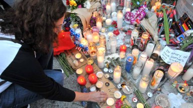 Candles and flowers were left at the base of the Hillcrest Pride flag after the speeches. Photo by Chris Stone