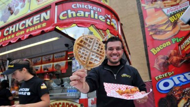 Tony Boghosian showing off the new food at Chicken Charlie's: chickne waffles and shrimp and rice kabob. Photo by Chris Stone