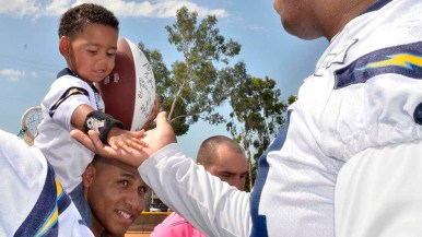 A child slaps hands with a Charger at Marine Corps Air Station Miramar. Photo by Chris Stone
