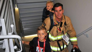 Timothy Wood of Rancho Santa Fe Fire District brings family members on the climb. Photo by Chris Stone