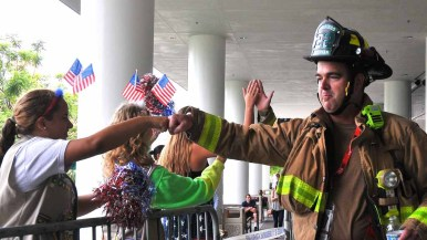 A San Diego firefighter fistbumps a Girl Scout who came out to cheer the climbers. Photo by Chris Stone