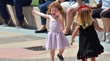 """Scarlett Sage Leitner, 2, of Scripps Ranch, and Adelle Jenna Brown, almost 3, of Pacific Beach dance at debut of """"Opera on Track."""" Photo by Chris Stone"""
