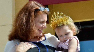 Julie Ludlum of San Carlos holds her 14-month-old daughter, wearing a tiara. She and her husband brought their children to the opera performance. Photo by Chris Stone