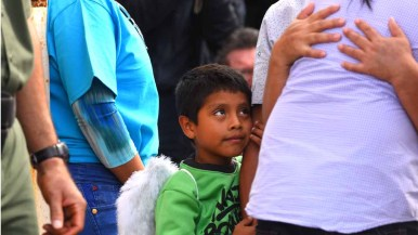 As Eduardo Hernandez hugs his son Luis, a young relative looks on. Photo by Chris Stone