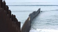 The U.S.-Mexico border fence stretches into the ocean. Photo by Chris Stone